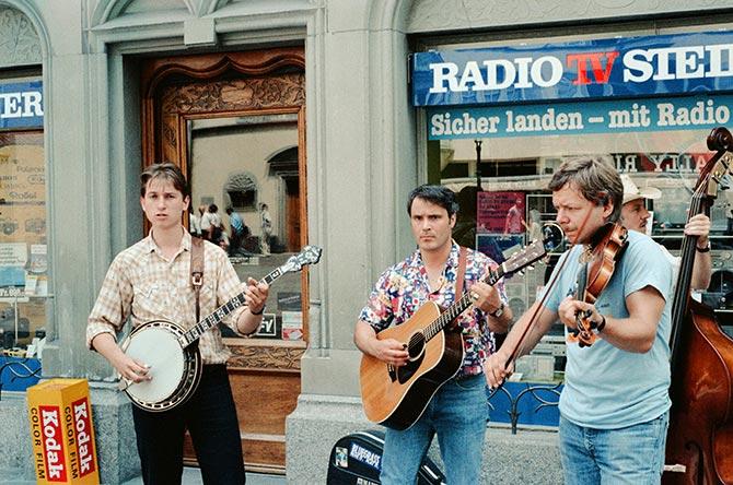 Jens Kruger on banjo, Fin Bodenmann on guitar, Christoph Kämpf on fiddle and Lorenz Gerber on bass playing bluegrass on the street in Lucerne, Switzerland, 1983.